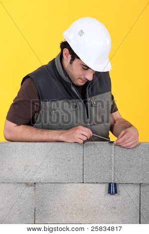 A mason using a plumb bob to check his wall.