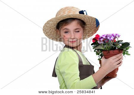 Little girl wearing straw hat holding plant pot