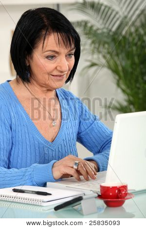 Middle aged woman at home using laptop