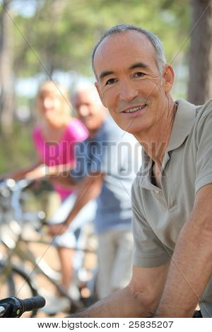Older man riding a bike in the forest with friends