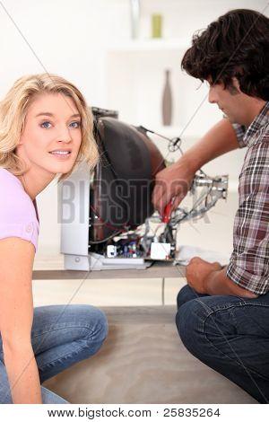 Electrician repairing broken television