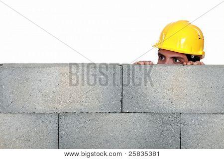 craftsman hiding behind a stone wall