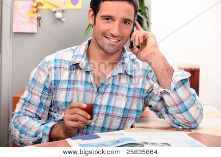 Man on the telephone having breakfast