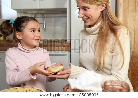 Little girl giving her mother a crepe