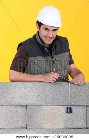 A mason checking his wall with a plumb bob.