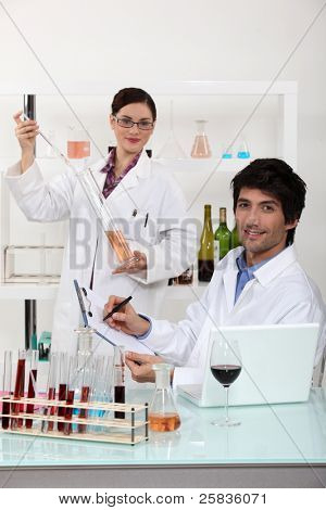 Man and woman testing wine in laboratory
