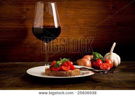 Bruschetta Aperitif mit Rotwein auf Holztisch