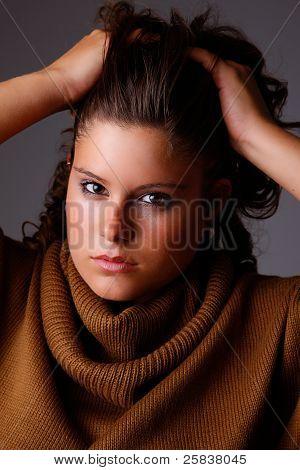 Hermosa mujer con manos sosteniendo el cabello, mirando a cámara, Studio Shot