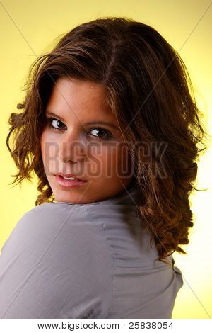 Young And Attractive Woman Looking To Camera, Isolated On Yellow, Studio Shot