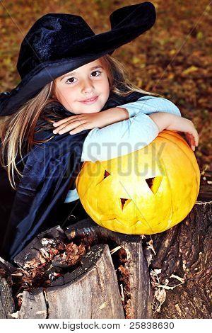 Tiro de una pequeña niña en traje de halloween con calabaza al aire libre.