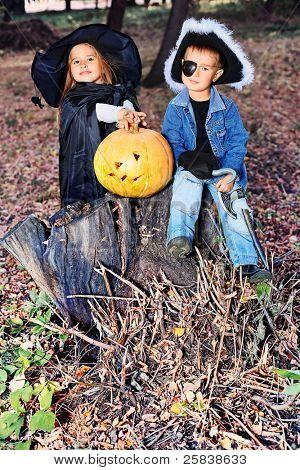 Toma de niños disfraces de halloween con calabaza al aire libre.