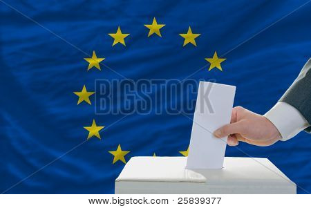 Man Voting On Elections In Europe In Front Of Flag
