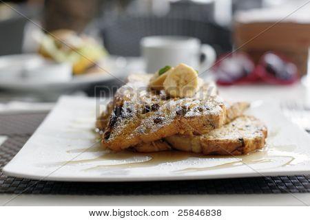 Torrija de canela con pasas de uva con jarabe de arce y plátanos francés