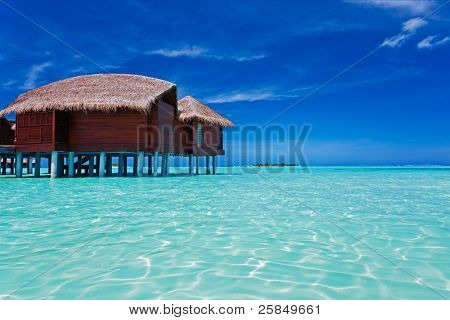 Overwater bungalow in blue lagoon around tropical island