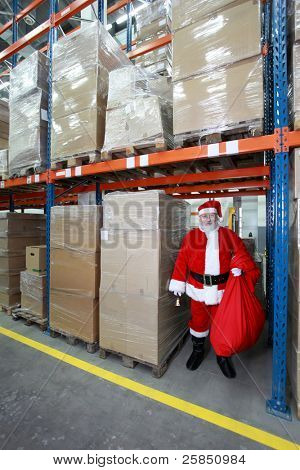 Santa Claus with large red sack and bell, ready for Christmas - waiting in storehouse