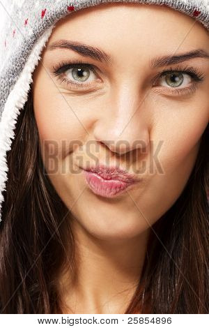 beautiful brunette woman wearing winter cap making puss face