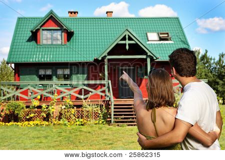 A picture of a young couple outside their new country house