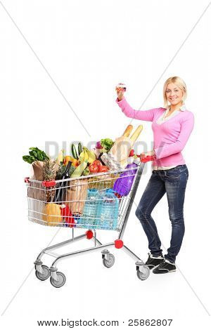Full length portrait of a smiling female showing a credit card and pushing a shopping cart isolated on white background