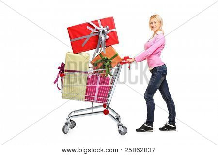 Young woman pushing a shopping cart full with gifts isolated on white background