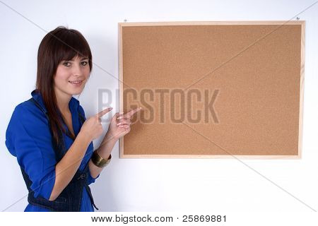 Happy girl pointing at the pin board.
