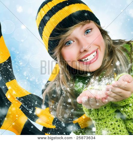 Christmas Girl.Winter Teenage girl Blowing Snow .New Year celebration