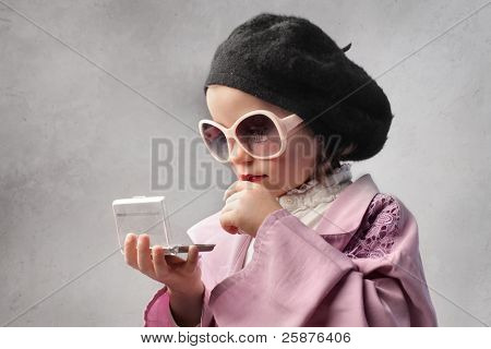 Little girl in fashion clothes looking at herself in a pocket mirror
