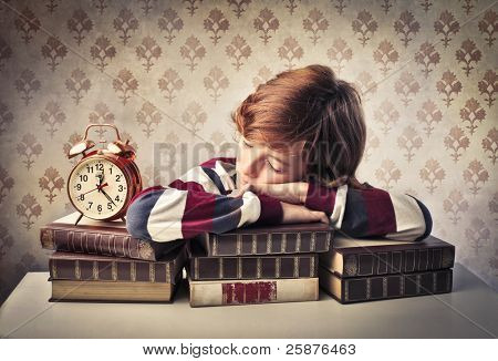 Child sleeping on a stack of books beside an alarm clock