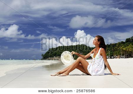 Attracrive girl sitting on the sand of a tropical beach