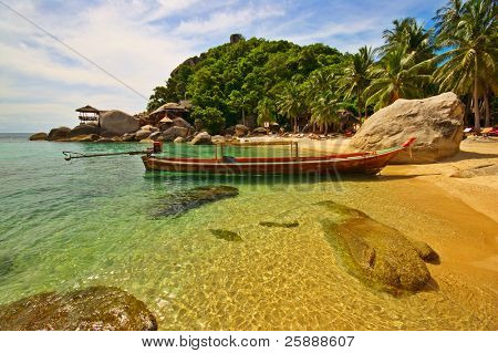 Exotic beach with long-tailed boat anchored at the shore