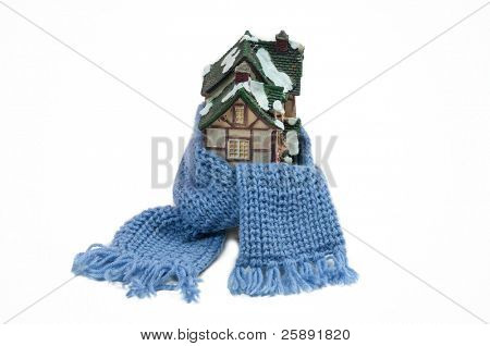 Christmas toy half-timbered house wrapped with scarf -  conceptual view of protecting or isolating house isolated on white background