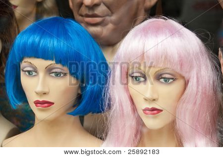 Two colorful wigs (blue and pink) in a wig store