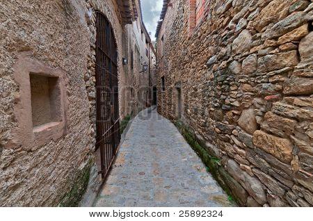 Narrow passageway between two walls in Peratallada, Spain