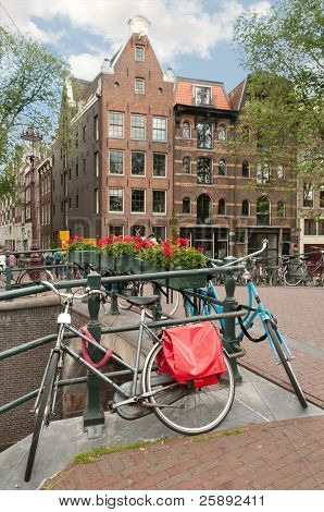 Bicycle parked on the bridge, in front of historic house in Amsterdam, Netherlands (Holland).