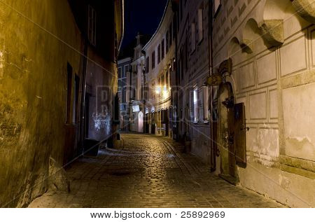 Narrow cobbled street in Cesky Krumlov at night, Czech Republic