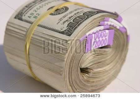 Ten Thousand Dollars American Cash rolled up and held together with yellow rubber band, as if laying on the ground for YOU the viewer!