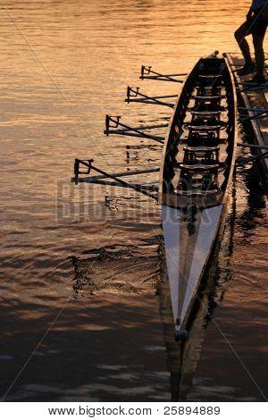 una persona con un barco de la fila a lo largo de la base con su pie en el amanecer de seattle