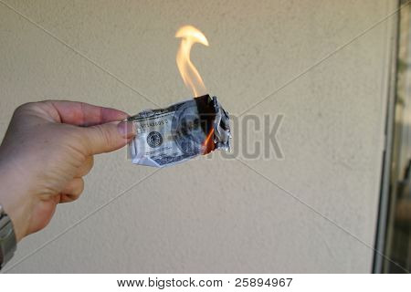 Money To Burn! A hand holding a One Hundred Dollar Bill on fire.