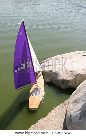a remote control sail boat glides gently upon the water