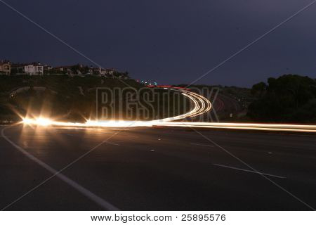 time laps (bulb exposure) of headlights heading towards the camera on an s-curved highway