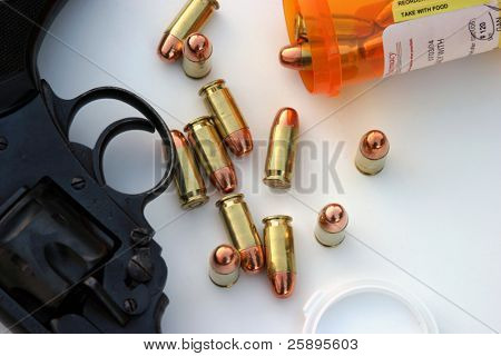 a partial view of a .45 cal hand gun lays on a white background with .45 ammo comming out of a medicine bottle