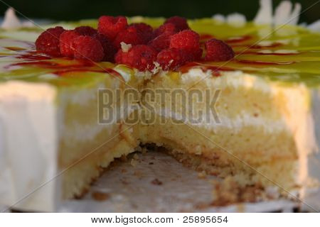 a deliscious lemon cake with raspberrys on top and frosting in the middle sits on a table at a wedding