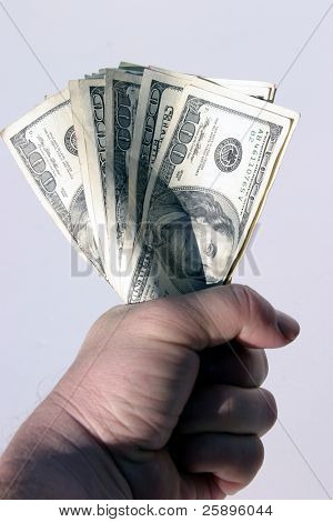 american cash being held tight in the fist of a real humanbeing against a white background
