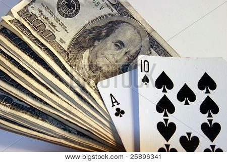 Twenty One hand laying on top of a pile of cash in $100.00 bills on a white background