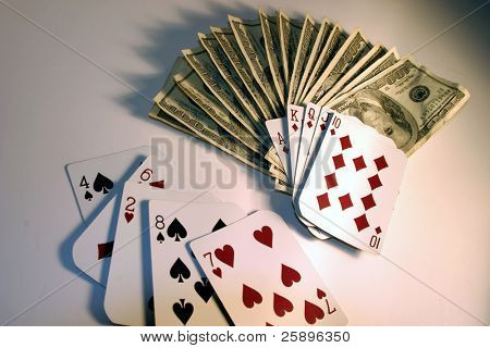 Royal Flush laying on a large pile of cash in $100.00 bills while a loosing hand lays next to it on a white background