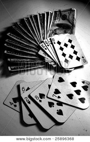Royal Flush laying on a large pile of cash in $100.00 bills while a loosing hand lays next to it on a white background.  in black and white for a special effect
