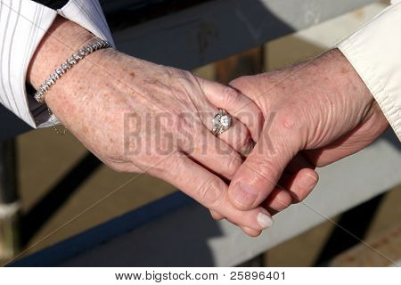 An older couple holds hands showing a wedding ring a brcelet and that love is in the air