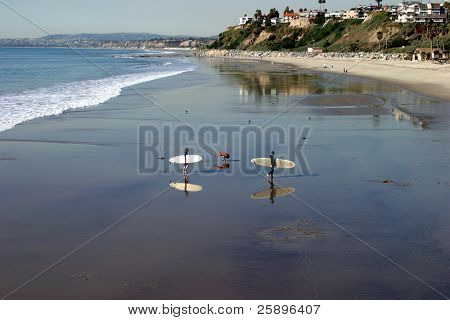somoene does what appears to be exercises on the beach while a couple of surfers walk past him, in the wet sand which creates great reflections