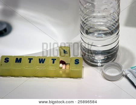 Pills in a weekly pill minder with an open bottle of water in a bathroom