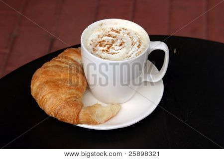 Latte with whipped cream and chocolate powder and croissant