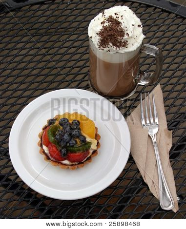Mocha Cappuccino with whipped cream chocolate powder and a fruit tart